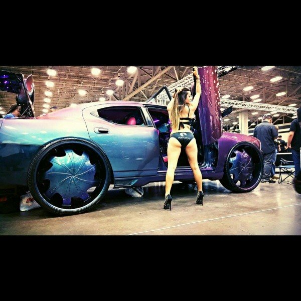 Chameleon Charger with Car show model posing next to it.